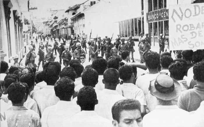 LA FOTO DE LA IZQUIERDA, TOMADA POCO ANTES DE QUE SE INICIARA LA MASACRE DEL 22 DE ENERO DE 1967 en las esquinas de los entonces bancos Central y Nacional. A la derecha, como es en la actualidad, sede de la Asamblea Nacional. Quedan algunos de los árboles de laurel de la india desde donde cayeron muertos muchos manifestantes. El primer muerto fue el teniente Sixto Pineda.